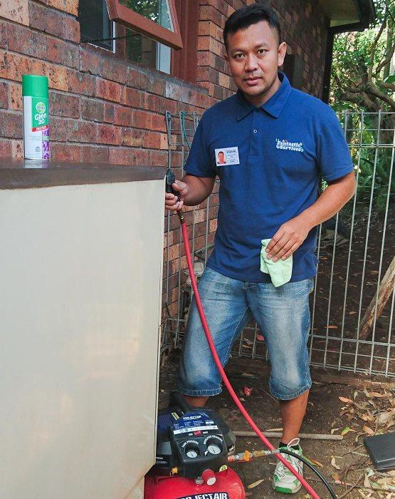 A Fantastic technician cleaning AC outdoor unit
