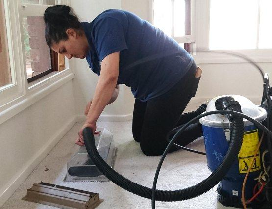 A fantastic worker using a vacuum to clean a vent and a duct on a floor