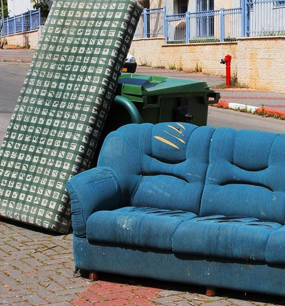 A mattress and a sofa stored outside for removal